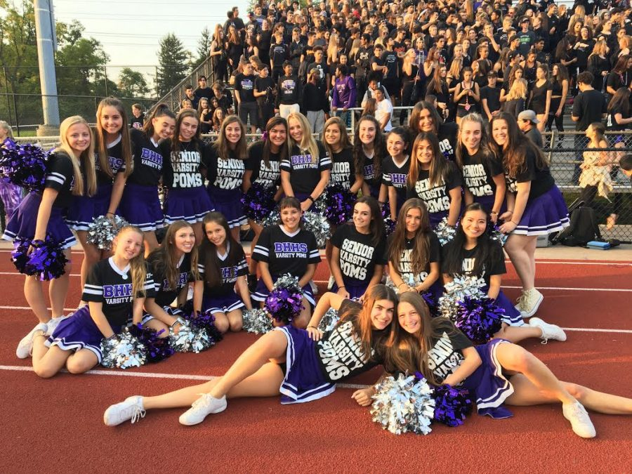 Varsity+poms+team+poses+with+the+student+section+at+football+game.