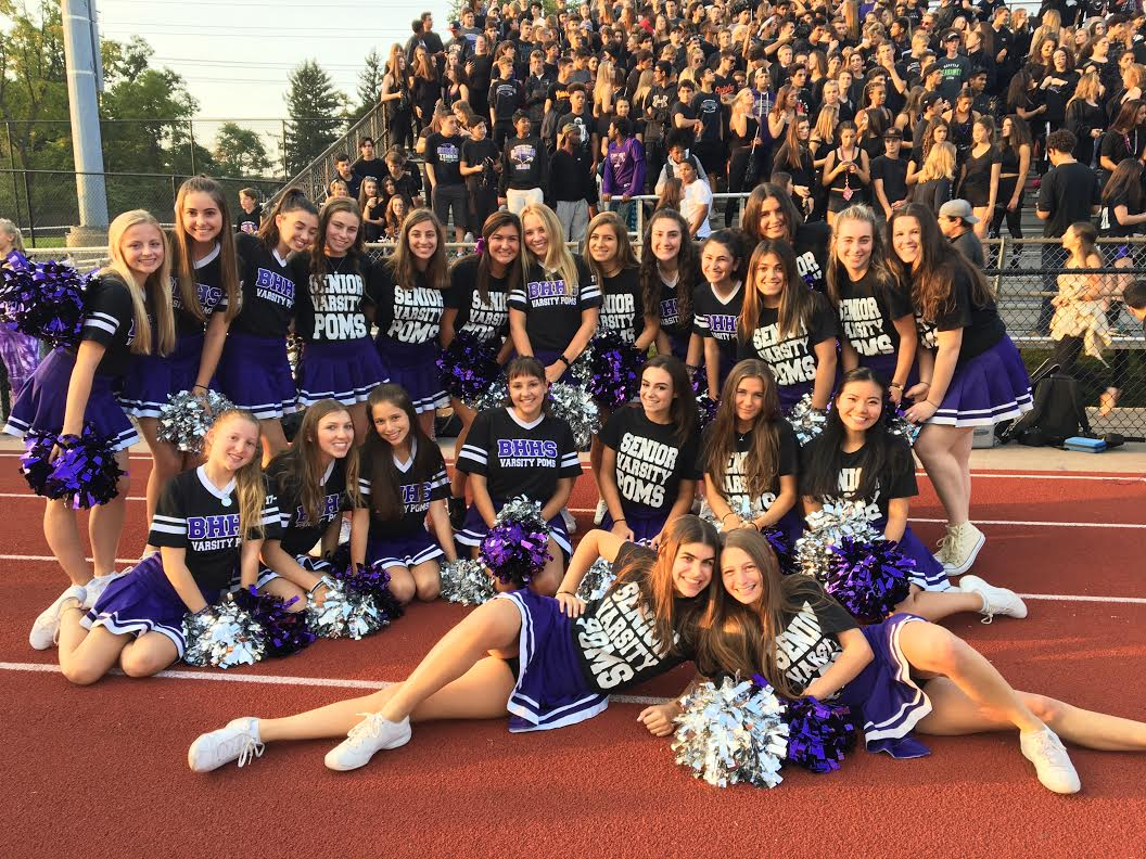 Varsity poms team poses with the student section at football game.