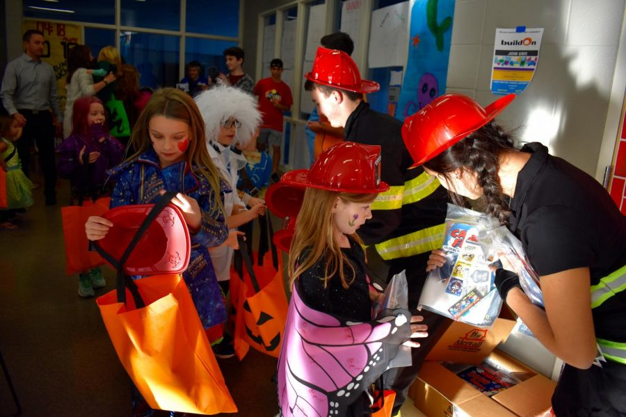 Bryce Gutowsky hands out candy to kids as a firefighter.