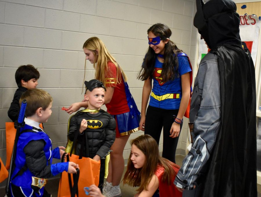 Milo Simmons and JP Arslanian face off, while Allie Yaker, Abby Sung, and Kylie Sitakis hand out candy.
