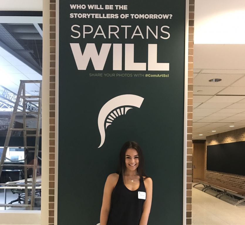 Lilly Swanson, senior, stands in Michigan State University's hallway with a smile.