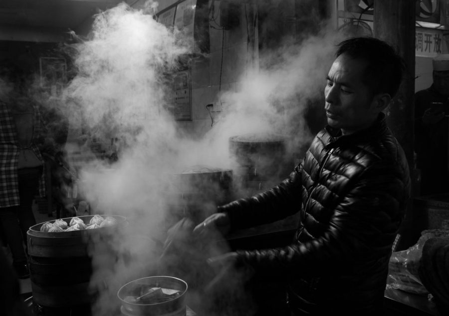 A street food vendor in XiAn, China, prepares steamed dumplings for sale on a bitter cold night.