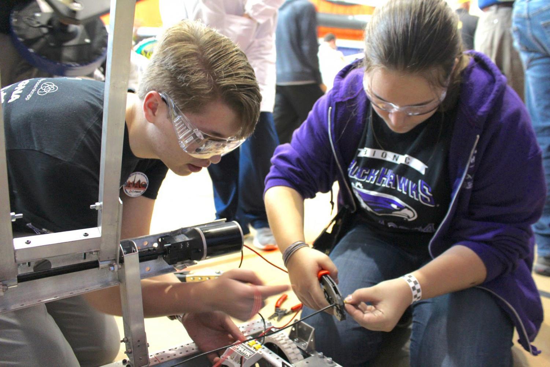 Sophmore Noah Casper and junior Sophie Henderson working on their robot.